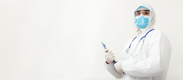 Коронавирус, ковид-19, прием к врачу. доктор в защитный медицинский костюм, биологическая опасность, маска для лица доктор с стетоскоп пишет на планшете. концепция медицинского здравоохранения. длинное белое знамя