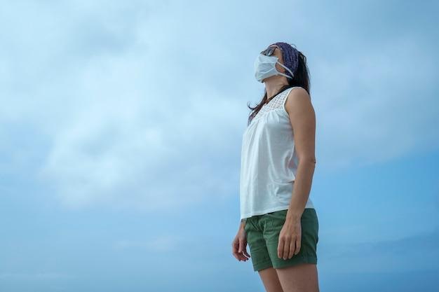Приморские каникулы коронавируса: снимок женщины на пляже, смотрящей на солнце с маской для пандемии ковид-19 с облачным небом