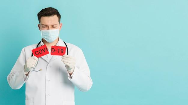 Заинтересованный доктор, разрывающий карточку ковид-19