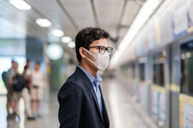 公共の駅で小説コロナウイルスまたはコロナウイルス病(コビッド19)に対する保護マスクを身に着けている若いアジア人男性は、呼吸器感染症を引き起こす伝染性ウイルスです。