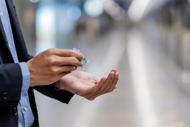 公共の駅で小説コロナウイルスまたはコロナウイルス病(コビッド19)に対する洗浄手消毒ジェルディスペンサーを使用して男の手