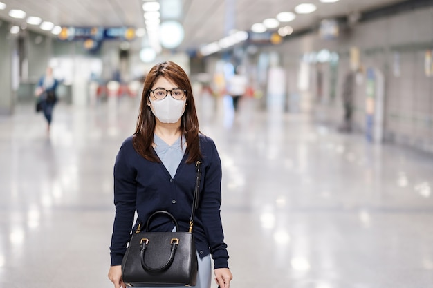 空港で小説コロナウイルスまたはコロナウイルス病(コビッド19)に対する保護マスクを身に着けている若いアジア女性