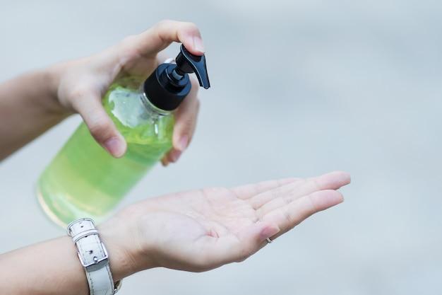 公共の屋内で小説コロナウイルスまたはコロナウイルス病(コビッド19)に対する洗浄手消毒ジェルディスペンサーを使用して女性の手。