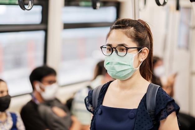 地下鉄の電車で小説コロナウイルスまたはコロナウイルス病(コビッド19)に対する手術用フェイスマスクを身に着けている若いアジア女性。