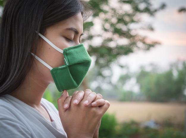 ウイルスを保護するためにマスクをかぶっているタイの女性、コヴィッド19世界がこの流行から安全であるために神からの祝福を祈る。