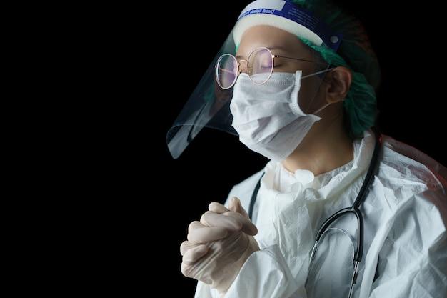 Доктор женщина молится о боже, чтобы желающие имели лучшее во время эпидемии ковид-19.