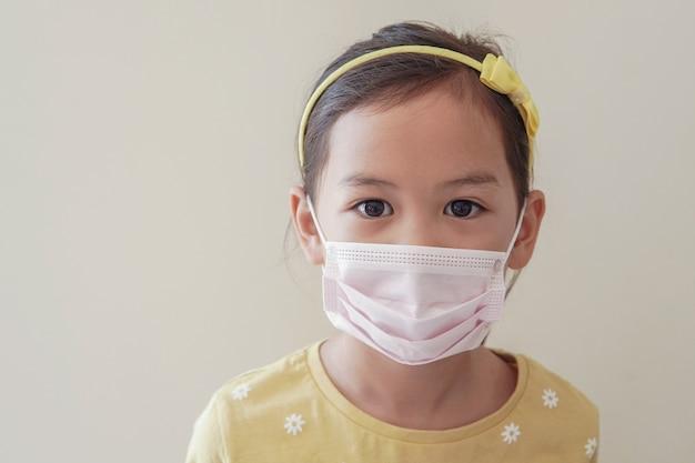 医療フェイスマスク、自己検疫、コロナウイルス、コビッド19ウイルスの流行流行パンデミックを身に着けているアジアの少女