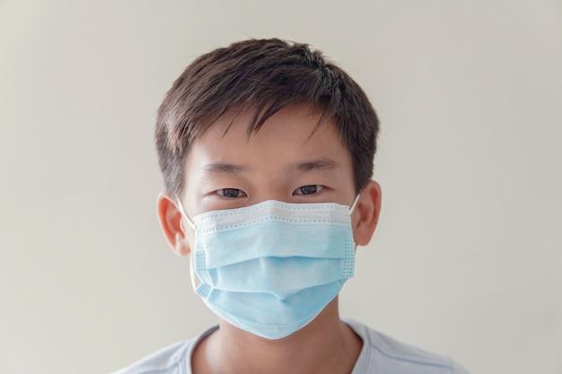 医療用フェイスマスク、自己検疫、コロナウイルス、コビッド19ウイルスの大流行流行パンデミックを身に着けているアジアのプレティーンの少年