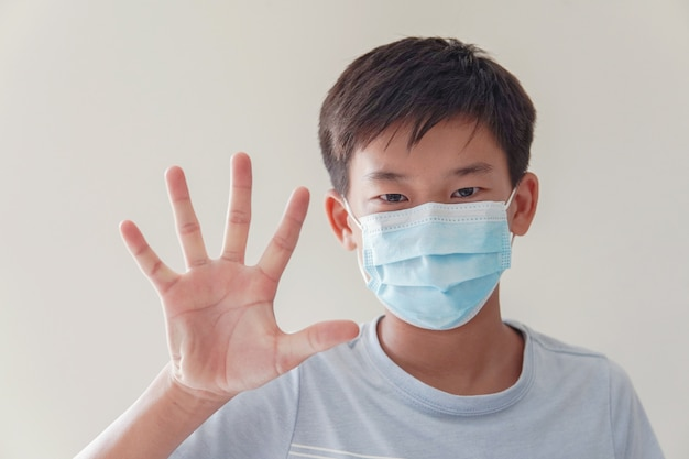 医療用フェイスマスクを着用し、一時停止の標識、自己検疫、コロナウイルス、コビッド19ウイルスの発生流行のパンデミックを作るアジアのプレティーンの少年