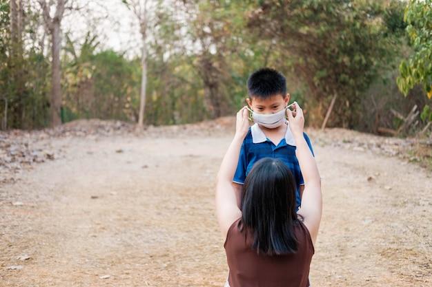 Мать носит маску, чтобы защитить сына от вируса ковид-19.