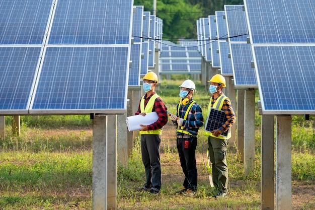 Инженер в защитной маске для защиты от ковид-19, работающий на проверке и обслуживании солнечной электростанции, солнечной электростанции, науки солнечной энергии.