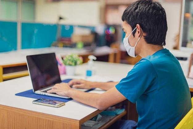 アジア人男性がコロナウイルスまたはコビッド-19の間に自宅で働いています。コロナウイルスから保護するためにフェイスマスクを着用します。