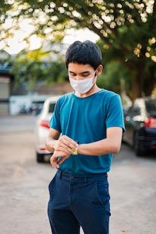 コロナウイルスやコビッド19から身を守るためにフェイスマスクを身に着けている男性は、時計を手首に向けて立っています。