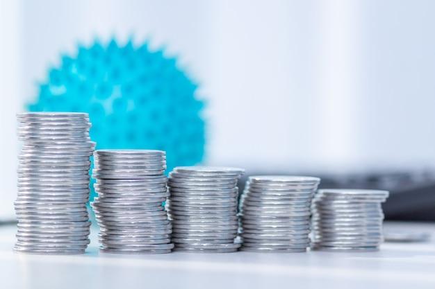 Влияние коронавируса на экономику. монеты, калькулятор на столе. медицина и деньги концепция, расходы на ковид-19.
