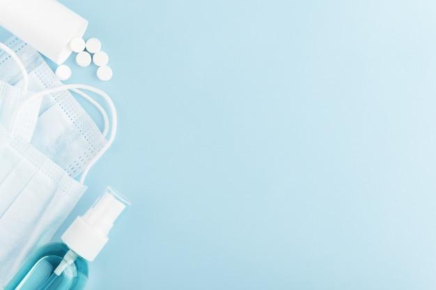 Медицинская защитная маска, антисептические и разбросанные антивирусные таблетки на фоне. ковид-19 и карантин.
