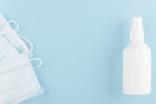 Белая марочная бутылка дезинфицирующего средства и медицинской защитной маски на столе. ковид-19 и карантин.