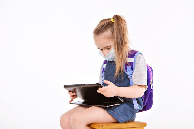 医療用マスクの1年生は読むことを学びます。家庭用遠隔学習の小さな女の子。