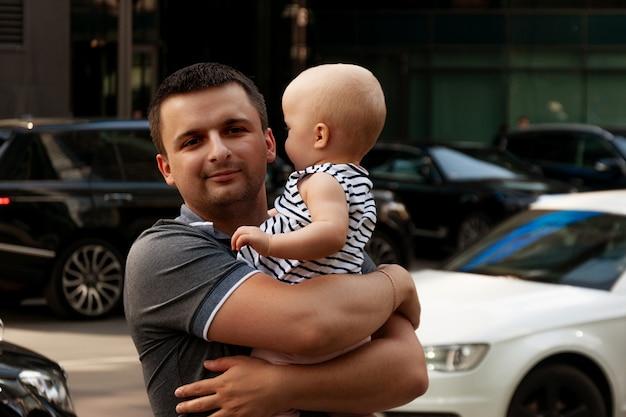彼の腕に1歳の赤ちゃんを持つ父。都市環境の中を歩きます。