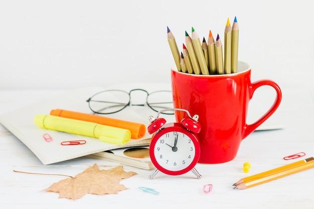 1 сентября концепт. красный будильник, чашка, цветные карандаши, очки и кленовый лист. вернуться к школьной концепции