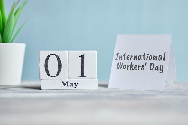 Праздник международный рабочий день - 1 мая первого месяца календарь концепции на деревянных блоков.