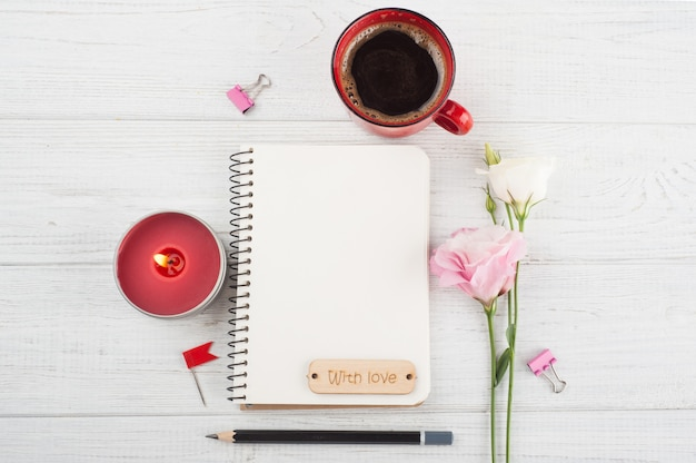 空白のノートブック、コーヒー1杯、ろうそく、花