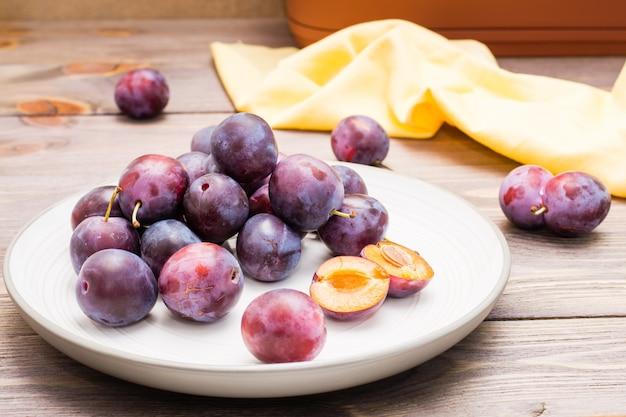 青いプラムの多くの全体の熟した果実と木製のテーブルの上のプレートに1つの二分されたベリー