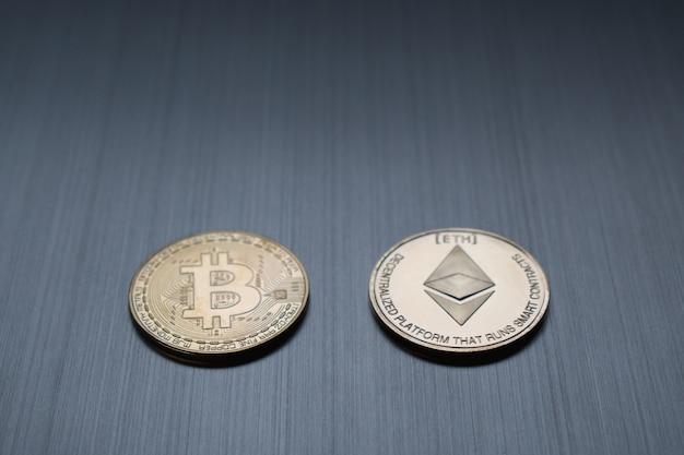 メタリックな背景に1つの黄金のビットコインとイーサリアムコイン