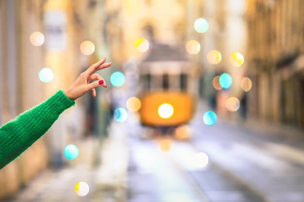 ポルトガルのリスボンの中心部にある古い路面電車の1つをビンテージスタイルで呼び出す旅行者