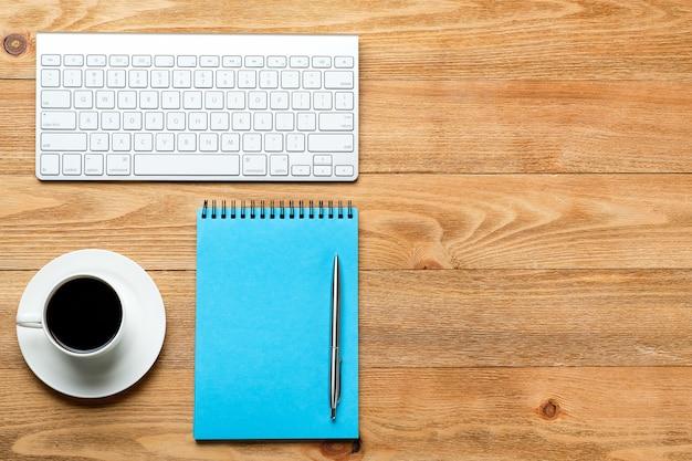 コンピューターのキーボード、メモ帳、ノート用のノート、木製のテーブルの上にコーヒーまたは紅茶1杯。職場のビジネスマンまたはマネージャーの仕事の主題。
