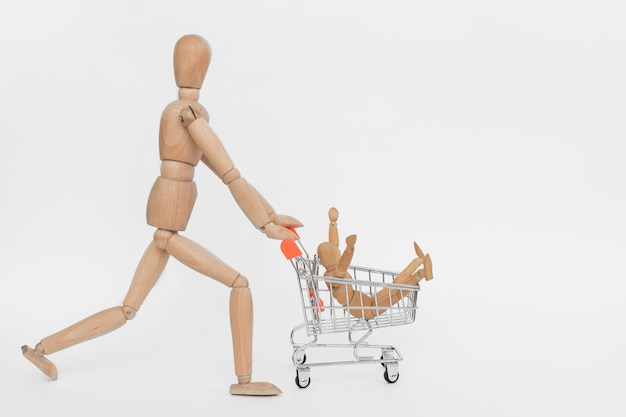 買い物中毒。別の1つに座っているショッピングカートに乗って木製の男。白で隔離