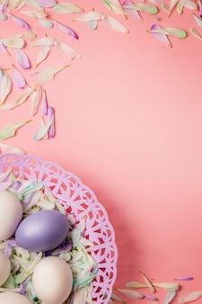 春の組成物。淡いピンクの背景のバスケットのイースターエッグ。 1つの卵は紫、他の卵は白