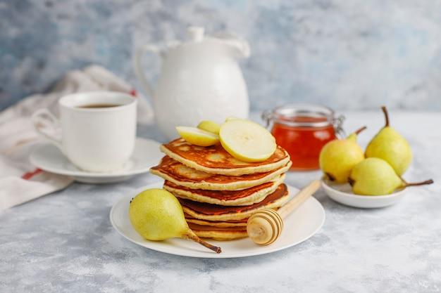 自家製の朝食:洋ナシと蜂蜜を添えたアメリカンスタイルのパンケーキ、コンクリートの上にお茶を1杯。トップビューとコピー