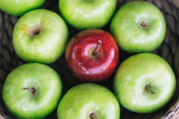 健康的なカラフルな青リンゴとバスケットの1つの赤いリンゴとそれぞれのおいしい利点のクローズアップビュー。異なる