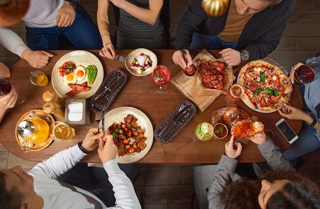 1つの大きなテーブルの食べ物を一杯食べるヨーロッパの友人のグループ