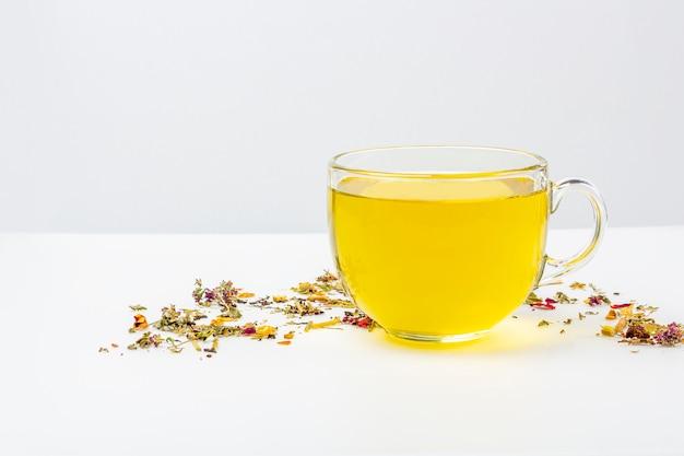 テキスト用のコピースペースで、白い背景の上に乾燥茶のヒープとガラスのマグカップで緑茶1杯を残します。茶道のためのオーガニックハーブ、フローラル、グリーンアジア茶。漢方薬のコンセプト