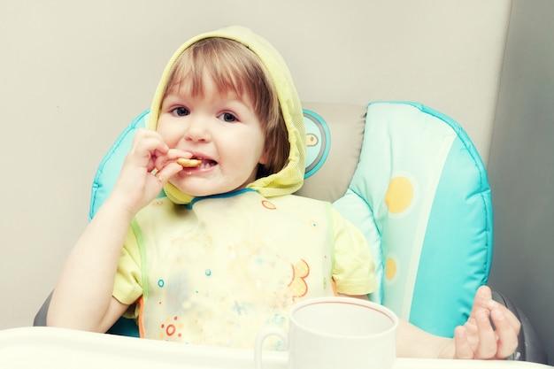1歳の小さな女の赤ちゃんがハイチェアで食べています。