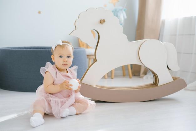 ピンクのドレスを着た1歳の少女は、子供の部屋で白いボールを手に持ち、揺れる馬のおもちゃの隣に座っています。
