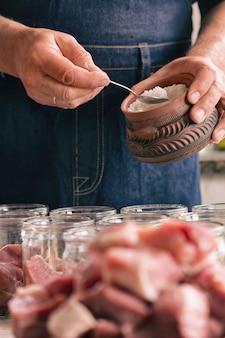 青いエプロンの男は肉に塩漬けをしています。塩小さじ1杯、缶詰用の肉の瓶。垂直。プロセスをクローズアップ