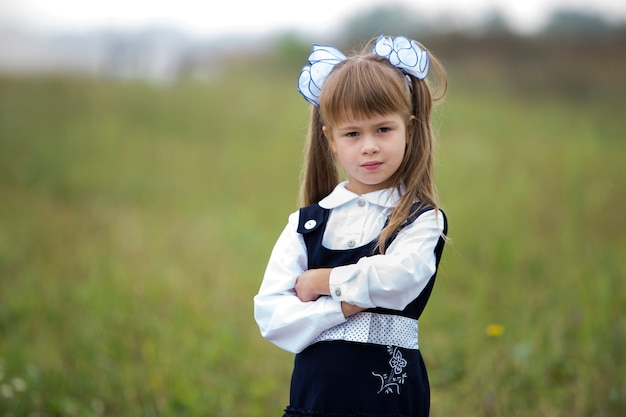 学校の制服を着たかわいい愛らしい自信を持って1年生の女の子と長いブロンドの髪に白い弓のクローズアップの肖像画。