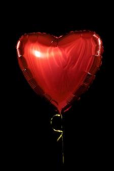 誕生日、バレンタインデーのための1つの大きな赤いハートボールオブジェクト。黒の背景に分離されました。