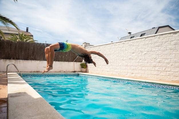夏休みの1日プールの水に飛び込む若いフィットネス男