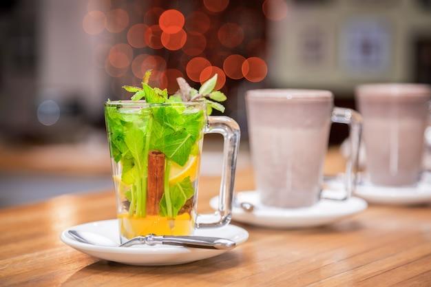 ミント、シナモン、白い皿のレモン入り紅茶1杯