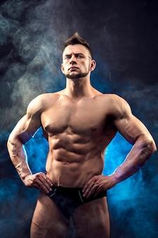 ロープを保持している筋肉の体を持つ1つのハンサムな性的な強い若い男