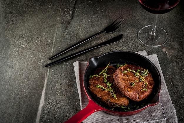 一人分のランチ。フォーク、ナイフ、ワイン1杯を添えて、フライパンにタイムを添えて自家製グリルビーフステーキを。黒い石のテーブル、トップビュー