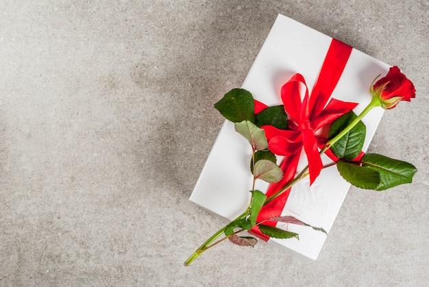 休日の背景、バレンタインの日。 1つの赤いバラのトップビューで包まれたギフトボックス