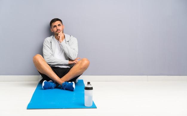 1つのアイデアを考えて床に座ってスポーツ男