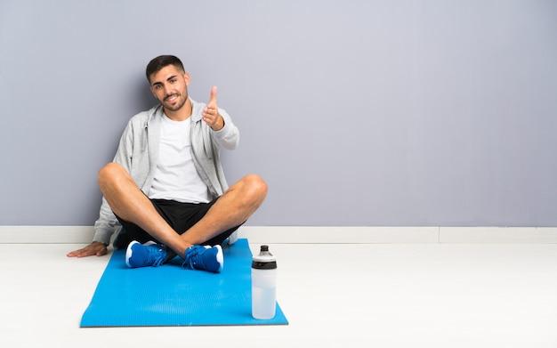 かなりの後に1つの床のハンドシェークに座ってスポーツ男