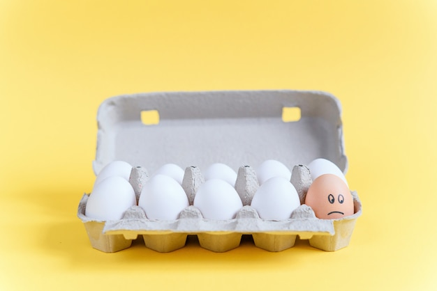 段ボールトレイの白い卵の中に描かれた悲しい顔をした1個のオレンジの卵。他とは違う。