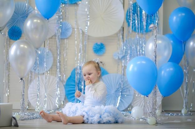 1歳の女の子の誕生日を祝います。青いスカートの女の子。