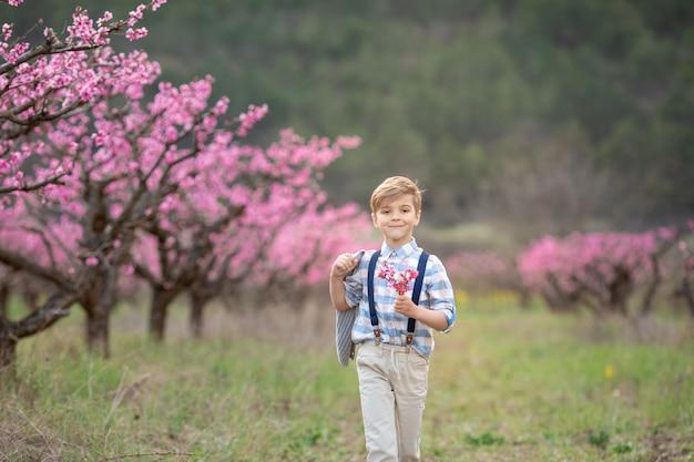 サスペンダー付きパンツで陽気なかわいい男の子1年生が春の庭を歩く